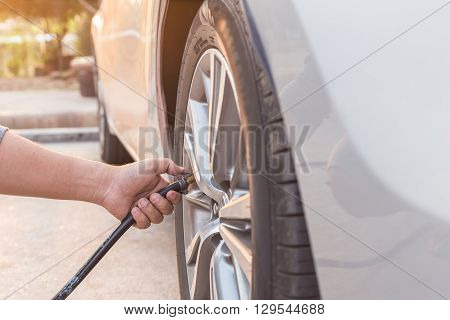 Man Checking Air Pressure And Filling Air To The Tires Of His Car