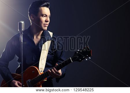 Professional male musician  plays and sing in the style of the sixties. Rock'n'roll, jazz man. Beat generation. Nostalgia.