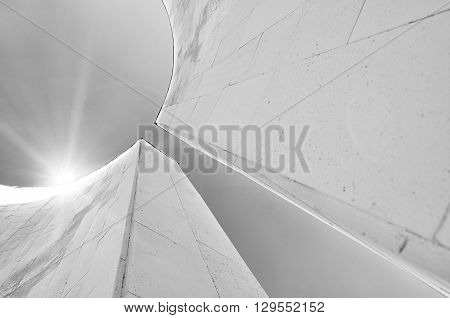 Bottom view of semicircular walls in futuristic urban style. Architecture urban background with reflected lights. Modern architecture cityscape black and white tones applied.