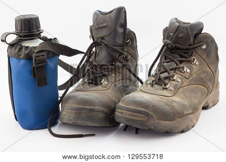 Close up of dusty worn hiking boots with water bottle on white