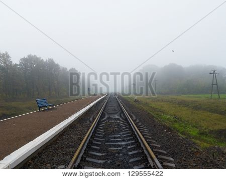 Empty railroad station platform with two benches on foggy day