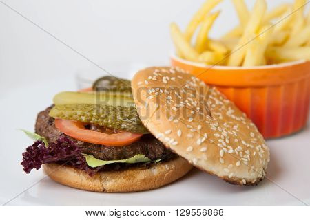 Hamburger with french fries on a white plate