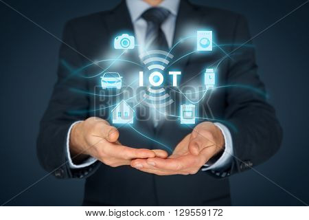 Internet of things (IoT) concept. Businessman offer IoT solution represented by symbol connected with icons of typical IoT - intelligent house car camera watch washing machine and cooker. poster