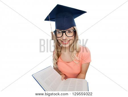people, education, knowledge and graduation concept - smiling young student woman in mortarboard and eyeglasses with encyclopedia book