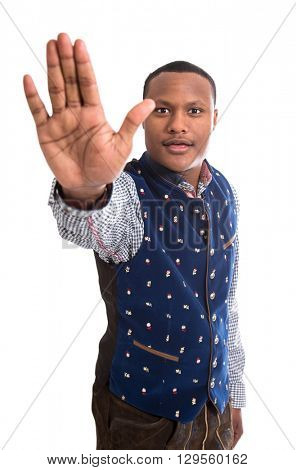 Stop says one isolated black man with his hand isolated over white background wearing typical bavarian clothes.