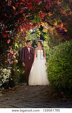 bride and groom in wedding attire against the backdrop of the garden at sunset, the bride crown princess