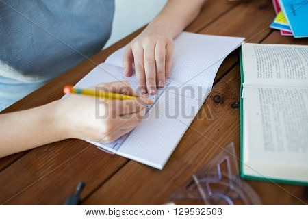 school, education, people and learning concept - close up of student or woman hands with ruler and pencil drawing line in notebook