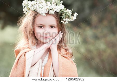 Smiling baby girl 4-5 year old wearing flower hairband outdoors. Looking at camera.