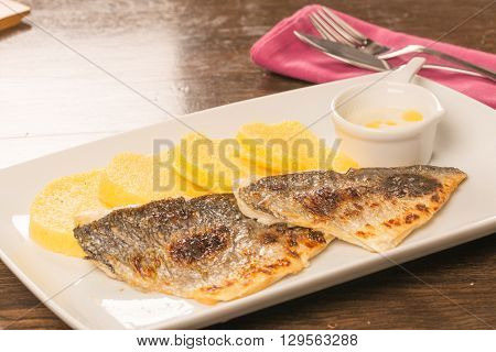 Grilled Fish Fillet With Polenta On A White Plate