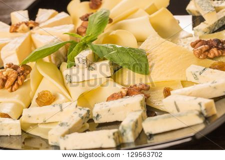 Close up with different types of cheese on a black plate