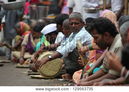 Pune India - July 11 2015: Hungry pilgrims called warkaris wait to be served on the streets during the famous wari pilgrimmage in India.
