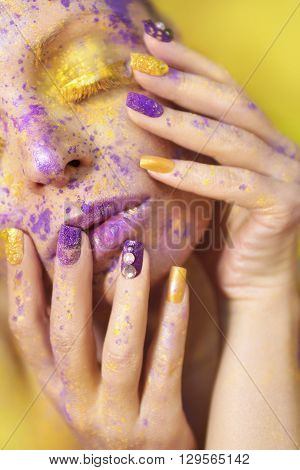 Makeup and manicure with a yellow lilac color on nails, face and body on a young woman.