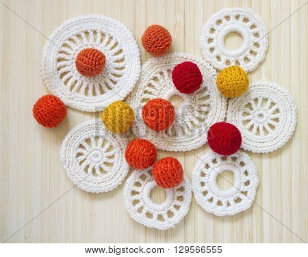 Red orange and yellow crochet beads and white vintage elements of Irish crochet. Cotton yarn for knitting crochet. Crochet doilies crochet pattern coasters on bamboo background