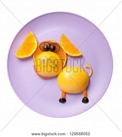Funny pig made of orange and grape on purple plate