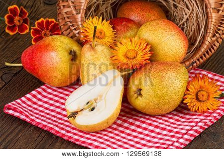 Autumn still life with pears and yellow flowers on rustic background.