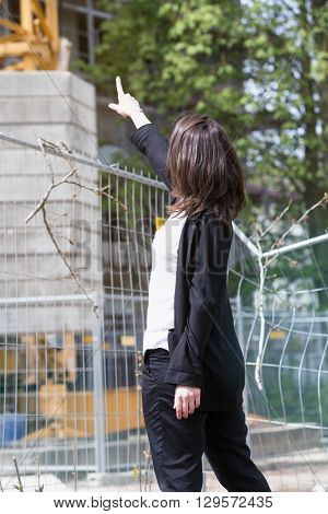 young woman standing in front of construction site and pointing at buidling
