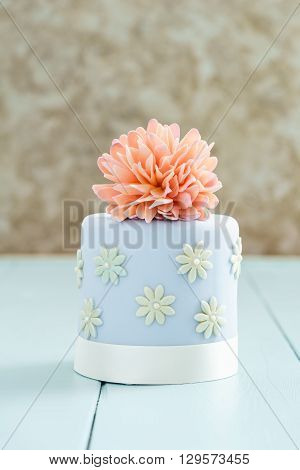 Blue fondant cake with pink sugar peony flower on blue table