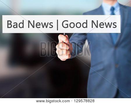 Good News Bad News - Businessman Hand Holding Sign