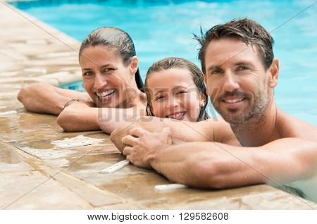 Pretty little girl with her parents in swimming pool. Happy family smiling and looking at camera in swimming pool. Portrait of a happy couple with daughter in swimming pool.