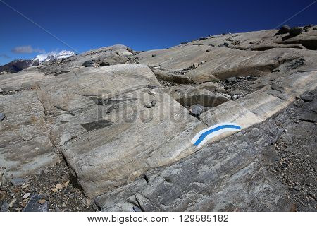 White and blue trail sign painted on a Rock. Saas-Fee. Swiss Alps