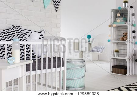 Baby bottle with milk in a bright baby room
