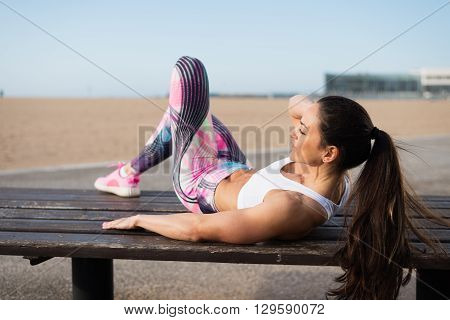 Fitness Woman Doing Crunches At The Beach