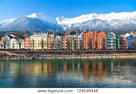 Austria Tyrol Innsbruck the Mariahilf strasse colored houses on the Inn river with the snowy mountains in the background