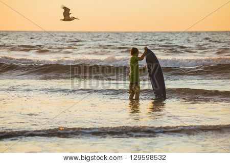 San Diego - November 7, 2015: Young boy surfer with board standing in ocean with flying pelican during sunset in San Diego, California