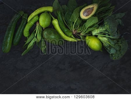 Raw green vegetables set. Broccoli, avocado, pepper, spinach, zuccini, lime on  dark stone background, top view, copy space