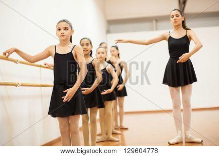 Cute little Hispanic girls listening to their teacher during a dance class