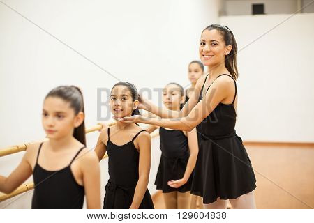 Portrait of a cute young Hispanic woman teaching little girls how to dance in a dance academy
