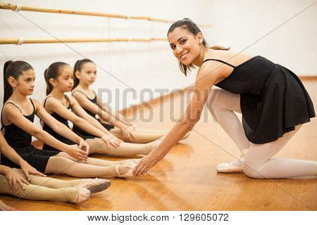 Portrait of a beautiful young dance teacher helping her students keep their feet together in a dance class