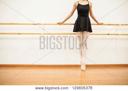 Ballet Dancer Tip Toeing Next To A Barre