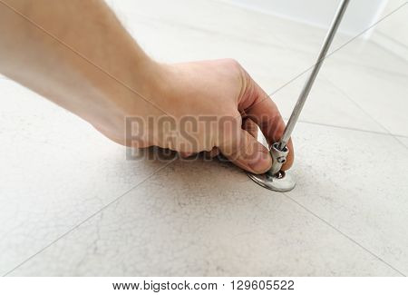 Worker uses a screwdriver to install the bracket for towel warmer.