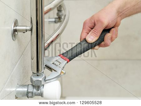 Plumber sets valve for towel warmer. It uses an adjustable wrench.