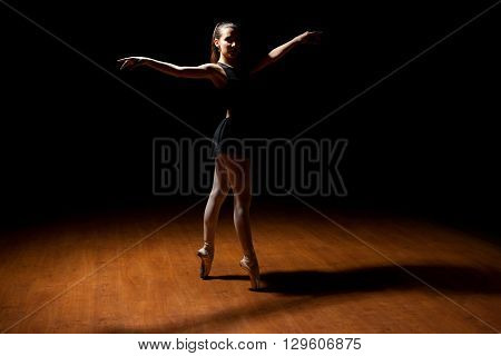 Young Ballet Dancer Standing In A Dark Stage