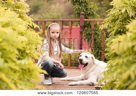 Smiling baby girl 3-4 year old sitting with dog on wooden floor outdoors. Looking at camera. Happiness.