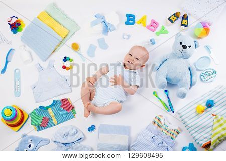 Baby on white background with clothing toiletries toys and health care accessories. Wish list or shopping overview for pregnancy and baby shower. View from above. Child feeding changing and bathing