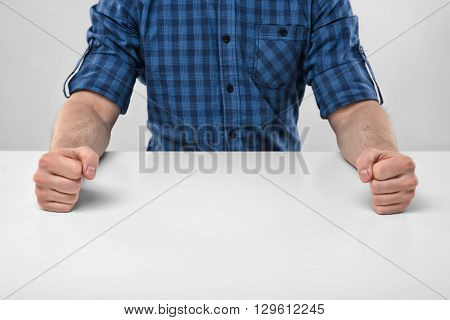 Closeup masculine fists clenched on the table. Anger sign. Nervous condition. Body language. Hand gesture. Aggression and threat. Defensive reaction.