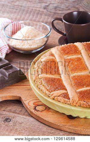 Image of chocolate coconut tart on wooden breadboard.