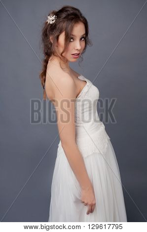Bridal fashion hairstyle and makeup. Brunette bride in wedding dress and beaded headpiece on gray backdrop.