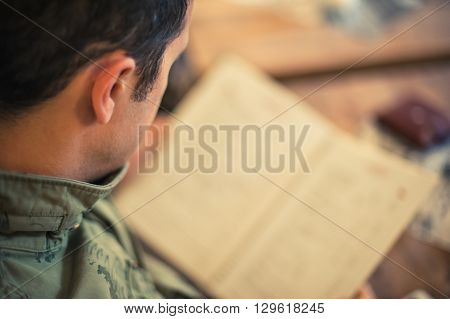 Young man looking at the menu in a restaurant . Close up