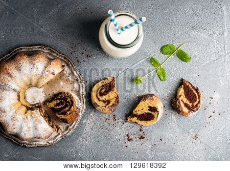 Zebra bundt cake cut into peices, milk in bottle and miny leaves over grey concrete textured background, top view