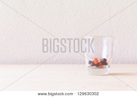 Pill In Glass On Wooden Floor And Concrete Background