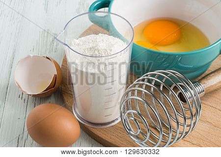 Chicken eggs, corolla of for whipping and flour on a wooden board on a light wooden background.
