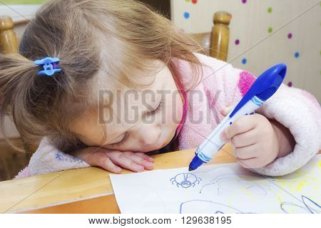 Little girl drawing beetle with blue marker