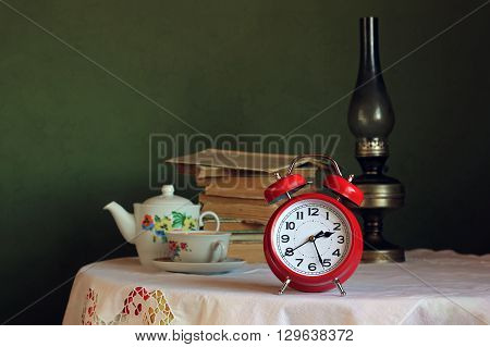 Red retro alarm clock on table with white tablecloth with lace. In the background a stack of books kerosene lamp and an old teapot and teacup for tea. Retro still life with alarm clock.