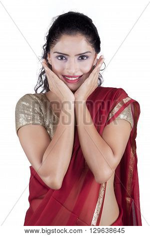 Pretty Indian woman smiling at the camera while wearing a red saree in the studio