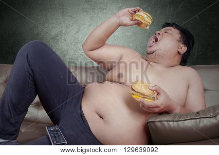 Picture of obese person looks hungry and eat two hamburger while leaning on the sofa