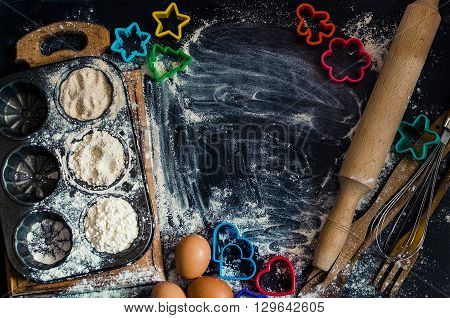 Baking cookies ingredients. Different kind of flour eggs colorful cutters egg beater and rolling pin on black chalkboard from above. Cooking course poster background - layout with free text space.